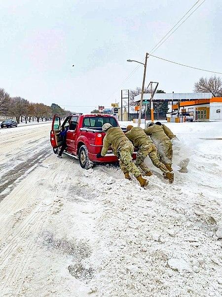 Gwardia narodowa wypycha samochód z zaspy w czasie burzy śnieżnej w Teksasie
