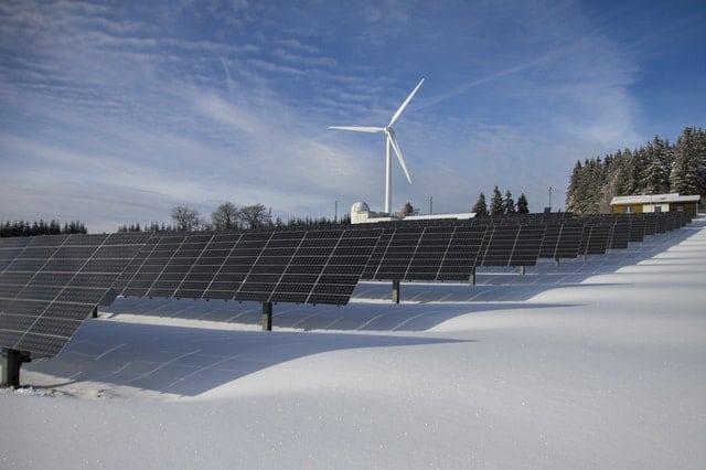 Energia odnawialna: panele słoneczne i turbiny wiatrowe w zimowym krajobrazie