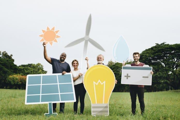 Społeczności energetyczne - na zdjęciu grupa osób trzymająca symbole różnych źródeł energii odnawialnej.